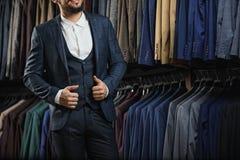 Zakenman in klassiek vest tegen rij van kostuums in winkel Royalty-vrije Stock Foto's