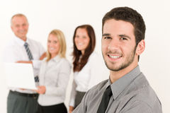 Zakenman knap met collega's in de rug Stock Afbeelding