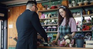 _zakenman kopen bloem in winkel en be*talen met krediet creditcard spreken glimlachen stock footage