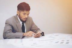 Zakenman in kostuum die op smartphone in bureau gebruiken Stock Foto's