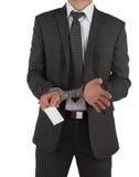 Zakenman in kostuum en handcuffs die kaart overhandigen Stock Fotografie