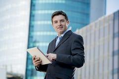 Zakenman in kostuum en stropdas digitale tablet houden die zich bevindt werkend in openlucht in openlucht bedrijfsdistrict Royalty-vrije Stock Afbeelding