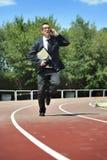 Zakenman in kostuum en stropdas dragende omslag in spanning op atletisch spoor die op mobiele telefoon spreken stock fotografie