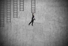 Zakenman in kostuum op ladder wordt gehangen die Stock Foto's