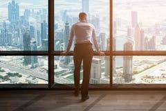 Zakenman Looking At Cityscape door Venster stock foto