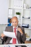 Zakenman Looking At Document bij Bureau royalty-vrije stock foto's