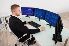 Zakenman Looking At Graph op het Computerscherm stock foto
