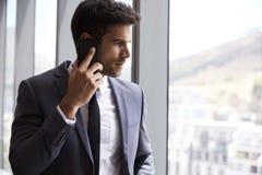 Zakenman Making Phone Call die zich door Bureauvenster bevinden stock foto