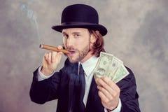Zakenman met bowlingspelerhoed in zwart kostuum die geld tonen en smok Royalty-vrije Stock Afbeelding