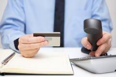 Zakenman met creditcard het draaien telefoon voor steun stock foto