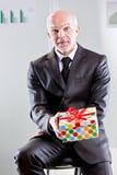Zakenman met een gift in zijn handen Stock Foto