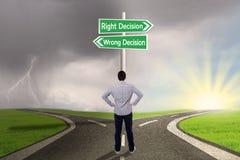 Zakenman met een teken van recht versus verkeerd besluit stock afbeeldingen