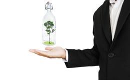 Zakenman met glasfles met een binnen boom, abstract die concept besparingenaard, op witte achtergrond wordt geïsoleerd Stock Afbeeldingen
