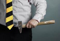Zakenman met in hand hamer en de werkende halsdoek van streek zwarte en gele strepen royalty-vrije stock foto's