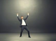 Zakenman met handen omhoog in de donkere ruimte Stock Fotografie