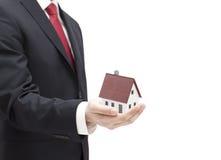 Zakenman met huis miniatuur in hand Stock Fotografie