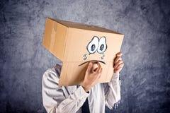 Zakenman met kartondoos op zijn hoofd en droevige gezichtsexpressi royalty-vrije stock foto