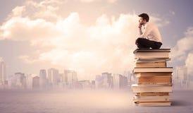 Zakenman met laptop zitting op boeken Royalty-vrije Stock Foto