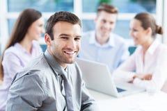 Zakenman met medewerkers op achtergrond Stock Foto's
