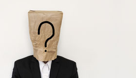 Zakenman met pakpapierzak op hoofd, met vraagtekensymbool met exemplaarruimte, op witte achtergrond Stock Afbeelding
