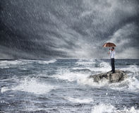 Zakenman met paraplu tijdens onweer in het overzees Concept verzekeringsbescherming stock afbeelding
