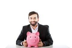 Zakenman met piggybank door een bureau Stock Foto