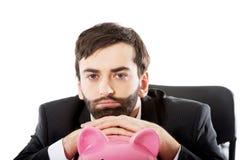 Zakenman met piggybank door een bureau Stock Foto's