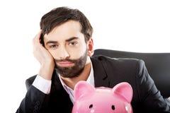 Zakenman met piggybank door een bureau Royalty-vrije Stock Foto