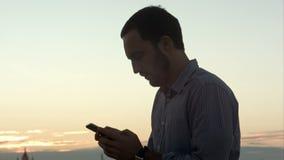 Zakenman met smartphone bij zonsondergang
