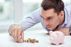 Zakenman met spaarvarken en muntstukken op kantoor Royalty-vrije Stock Afbeelding