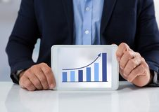 Zakenman met tablet bij bureau en grafiekpijl Stock Afbeelding