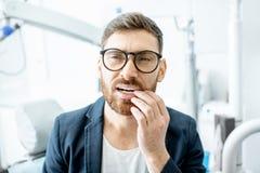 Zakenman met tandpijn in het tandbureau stock foto