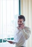Zakenman met telefoon voor het venster Stock Foto