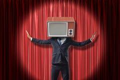 Zakenman met uitstekende TV-reeks die in plaats van hoofd wapens op de rode achtergrond van stadiumgordijnen opheffen stock foto's