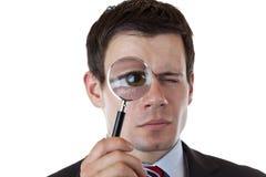 Zakenman met vergrootglas bij oog stock afbeeldingen