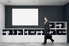 Zakenman in modern bureau met lege affiche Royalty-vrije Stock Foto's