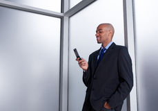 Zakenman naast een venster dat celtelefoon bekijkt royalty-vrije stock afbeeldingen