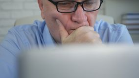 Zakenman In Office Room die Ongerust gemaakte Studie Elektronische Documenten kijken stock afbeelding