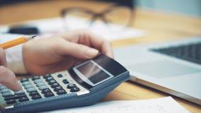 Zakenman om de kosten te berekenen en financiën in het bureau te maken, de taak van financiënmanagers, het bedrijfsconcept stock video