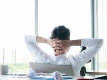 Zakenman ontspannend concept: zakenmanzitting met voeten omhoog bij bureau die uit venster in time rust kijken royalty-vrije stock foto