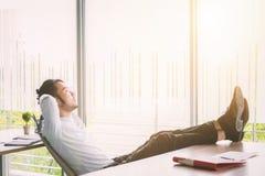 Zakenman ontspannend concept: zakenmanzitting met voeten omhoog bij bureau in rusttijd royalty-vrije stock foto