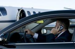 Zakenman op celtelefoon in luxeauto Stock Afbeelding