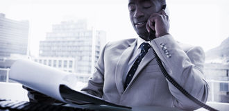 Zakenman op de telefoon terwijl het lezen van een document Royalty-vrije Stock Fotografie