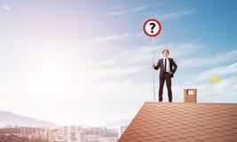 Zakenman op het dak die van het baksteenhuis banner met vraagteken tonen Gemengde media Royalty-vrije Stock Afbeeldingen