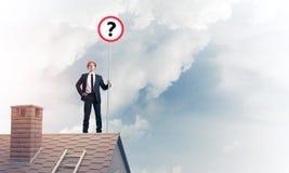 Zakenman op het dak die van het baksteenhuis banner met vraagteken tonen Stock Foto's