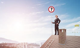 Zakenman op het dak die van het baksteenhuis banner met vraagteken tonen Gemengde media Stock Fotografie