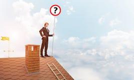 Zakenman op het dak die van het baksteenhuis banner met vraagteken tonen Gemengde media Royalty-vrije Stock Foto's