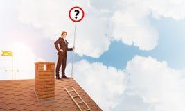 Zakenman op het dak die van het baksteenhuis banner met vraagteken tonen Gemengde media Royalty-vrije Stock Fotografie