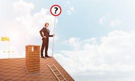 Zakenman op het dak die van het baksteenhuis banner met vraagteken tonen Gemengde media Stock Afbeeldingen