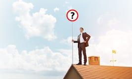 Zakenman op het dak die van het baksteenhuis banner met vraagteken tonen Gemengde media Stock Foto's